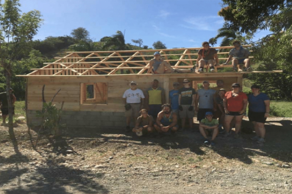 Group of Missionaries standing in front of the newly built house frame
