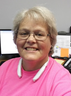 women smiling wearing glasses and pink shirt